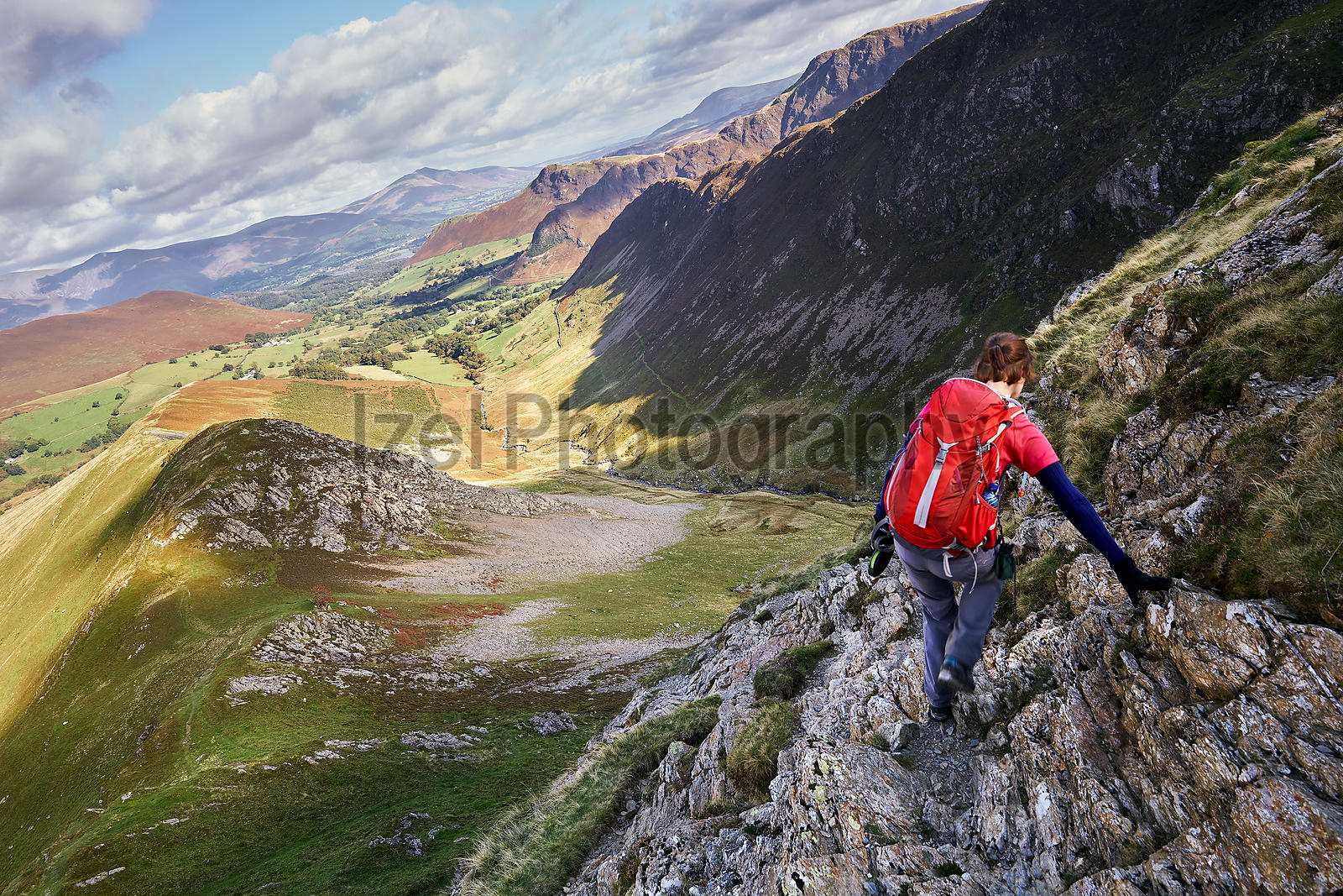 A hiker scrambling down towards High Snab Bank from the summit of Robinson in the Lake District, England, UK.