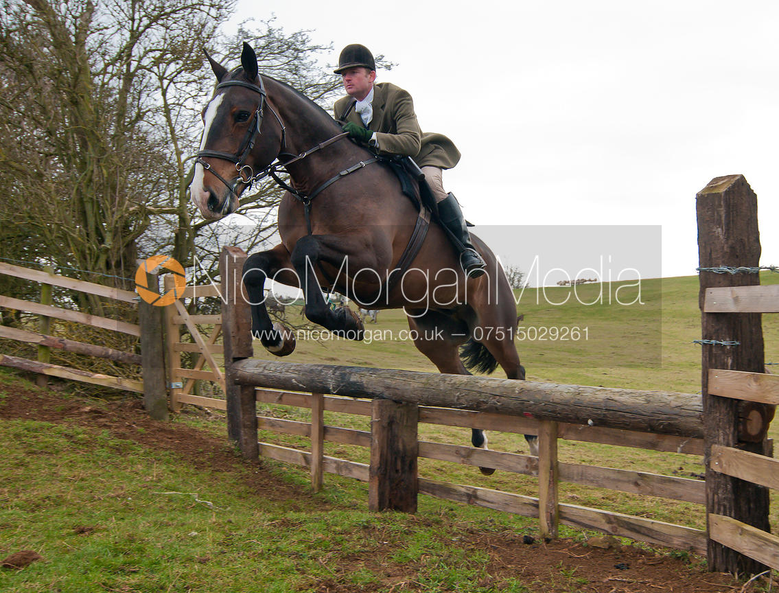 Capt Max Chenery - Cottesmore Hunt followers jump a hunt jump near Somerby