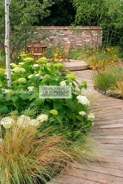 terrasse dans un jardin anglais alle en bois massif avec hydrangea hortensia