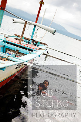 Child swimming next to pump boat on shore line of Taal Volcano Island, Lake Taal, Talisay, Batangas, Philippines