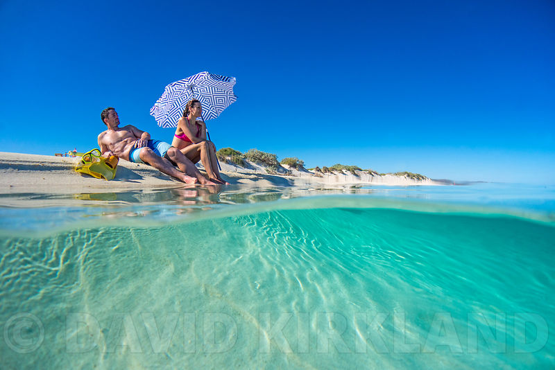 248a2743d33 Couple sunbaking on the beach