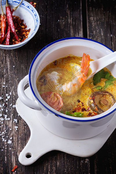 White plate with spicy thai soup tom yam with coconut milk, chili pepper and shrimp over white marble as background