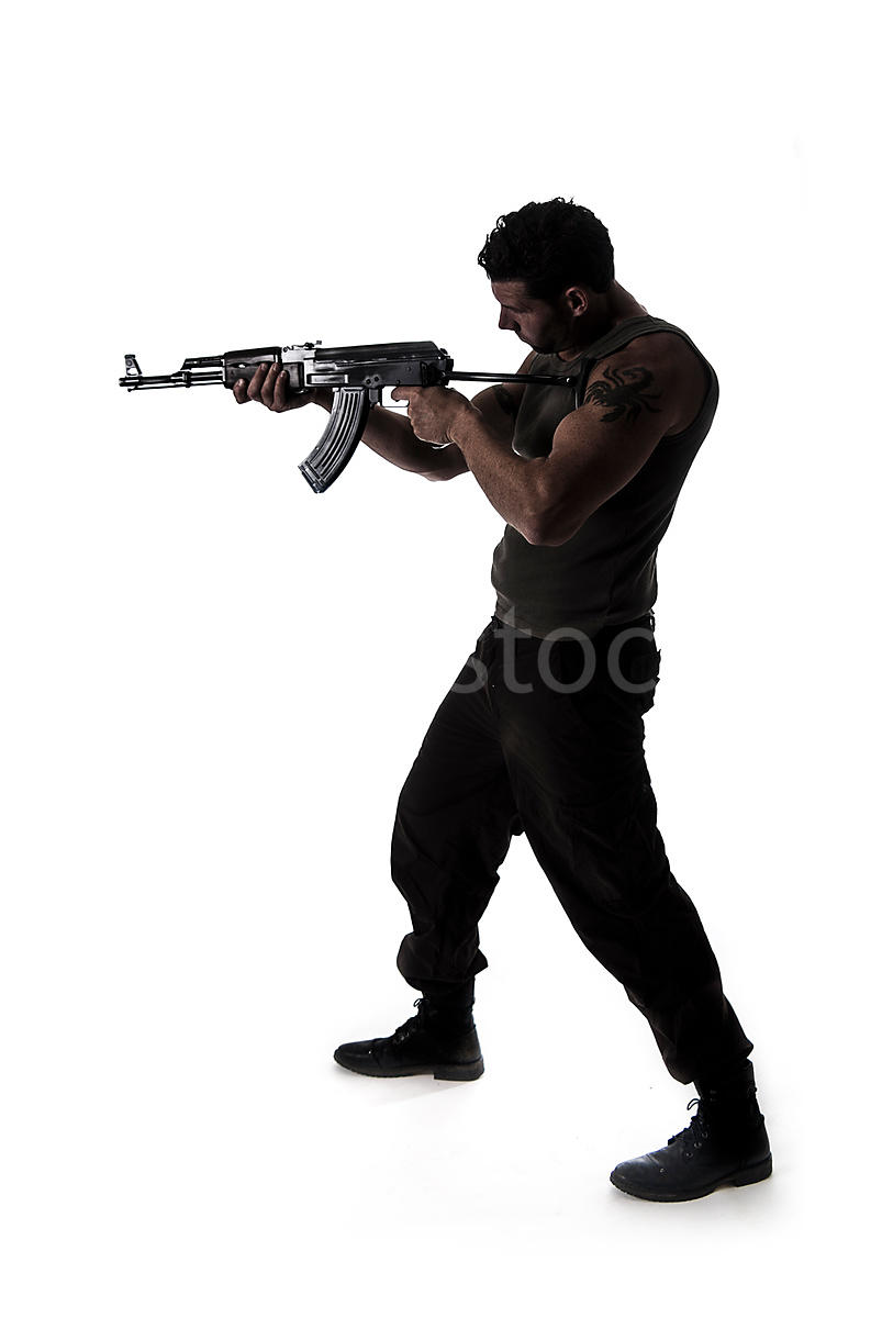 figurestock a silhouette of a man standing and pointing an ak 47