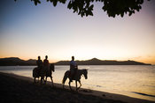 Dusk over Barcelo Langosta Beach with toursit on horses, Tamarindo, Costa Rica