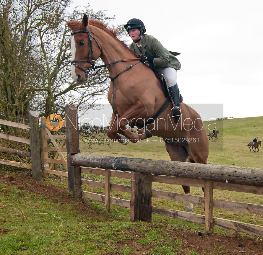 Cottesmore Hunt followers jump a hunt jump near Somerby