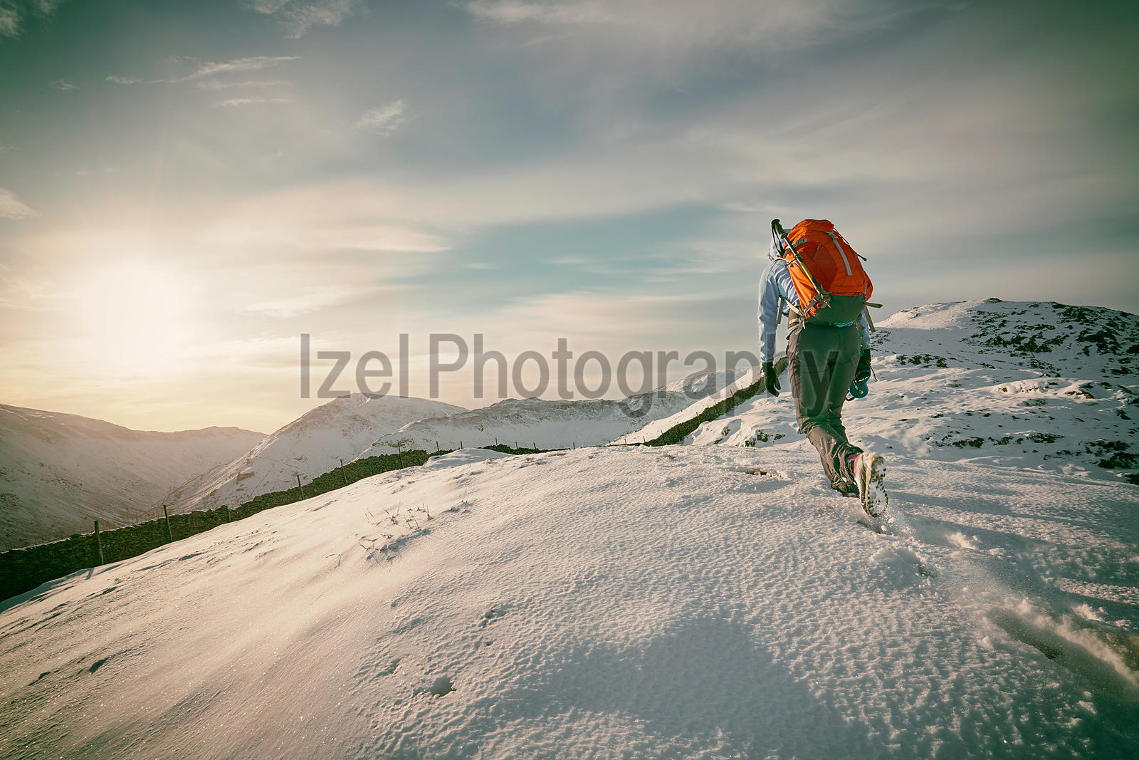 A hiker making their way up a snow covered ridge.