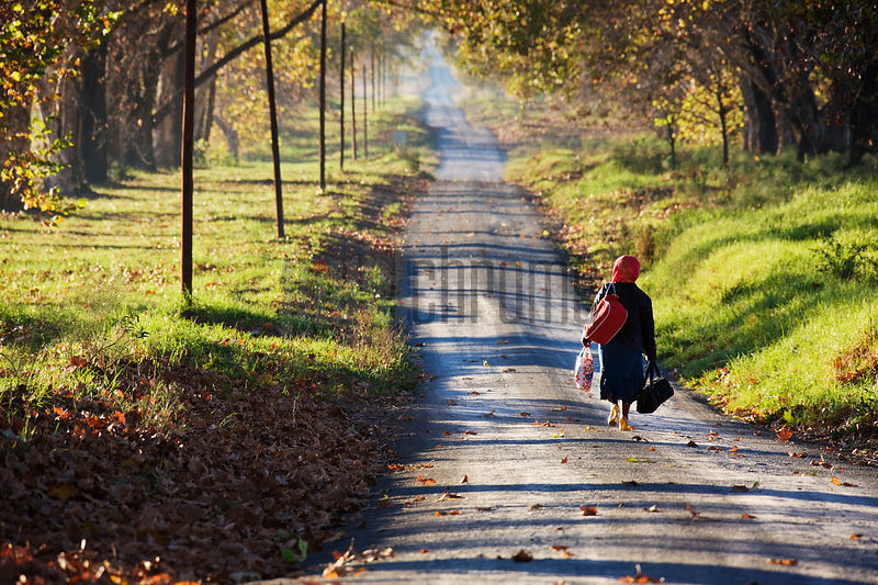 Woman Walking Down Dirt Road