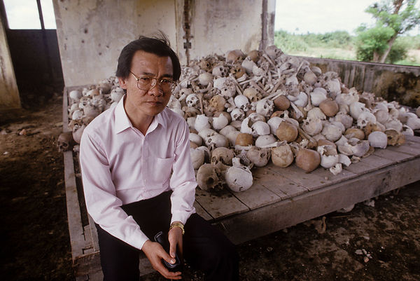 He sits by a pile of skulls and bones of executed victims of the Pol