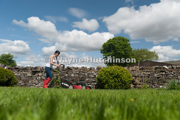 Wayne Hutchinson Photography Lady mowing garden lawn with petrol