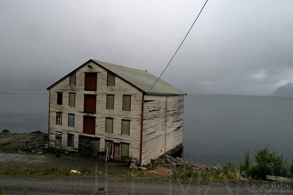 Old abandonned wooden house by a fjord