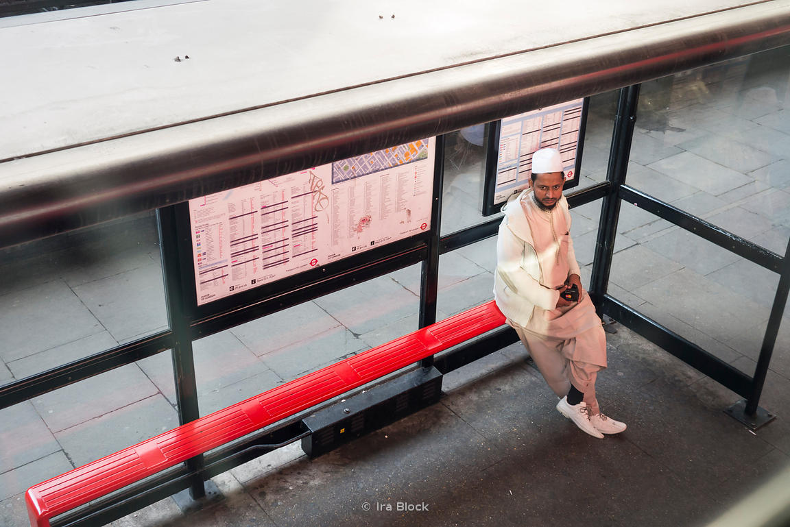 ira block photography | an arabic man sitting on a bench at a bus