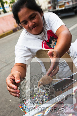 Street scene in Kaibigan neighborhood with women and mouse, San Andres Bukid, Manila, Philippines