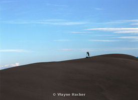 An unknown photographer waiting for his shot. Standing in the Great Sand Dunes National Park of Colorado's Rocky Mountains.