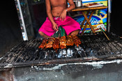 Street scene in Kaibigan neighborhood with vender and grill, San Andres Bukid, Manila, Philippines