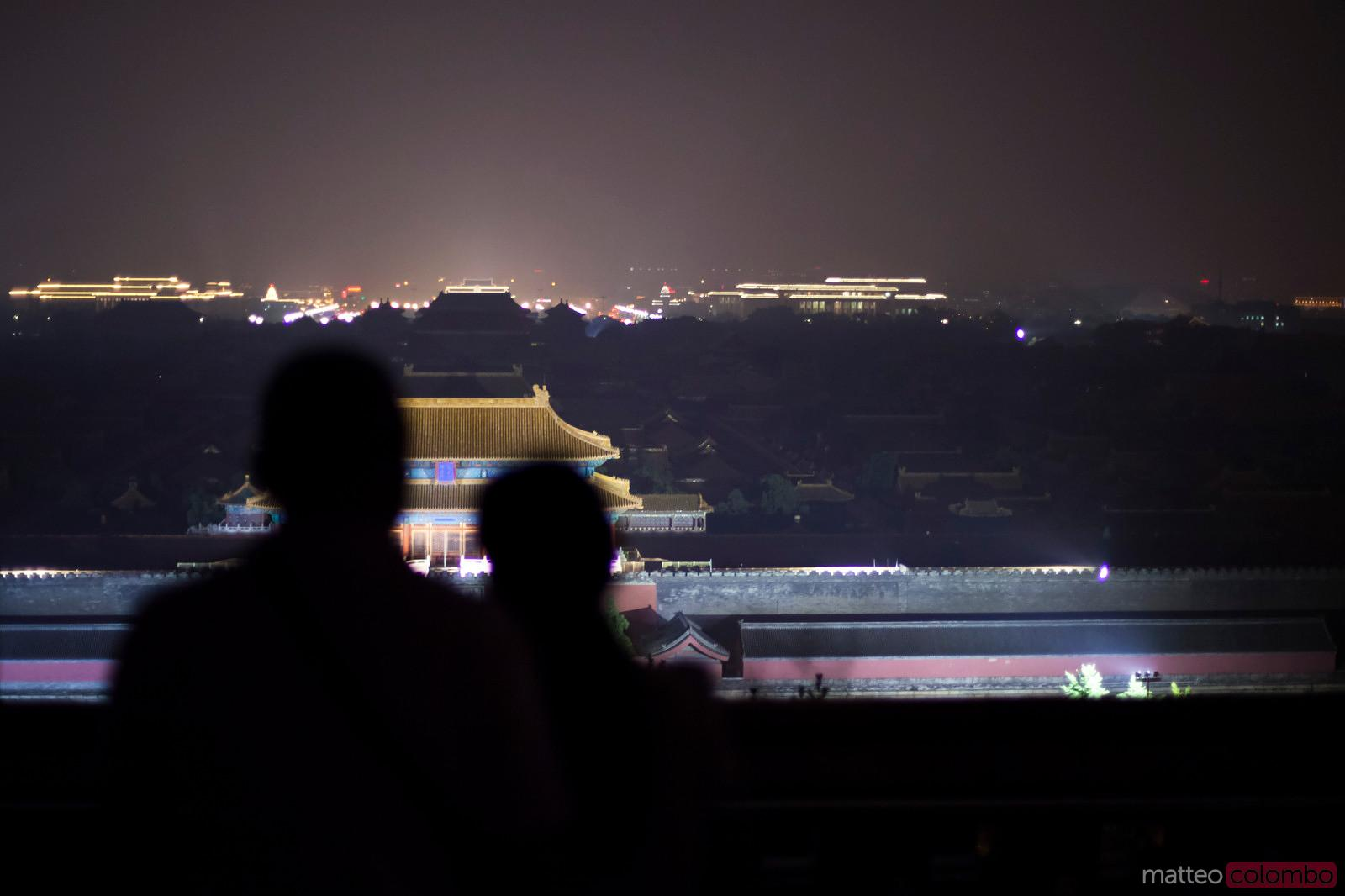 Couple watching the forbidden city at night