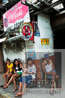 Street scene in Kaibigan neighborhood with group of people sitting, San Andres Bukid, Manila, Philippines