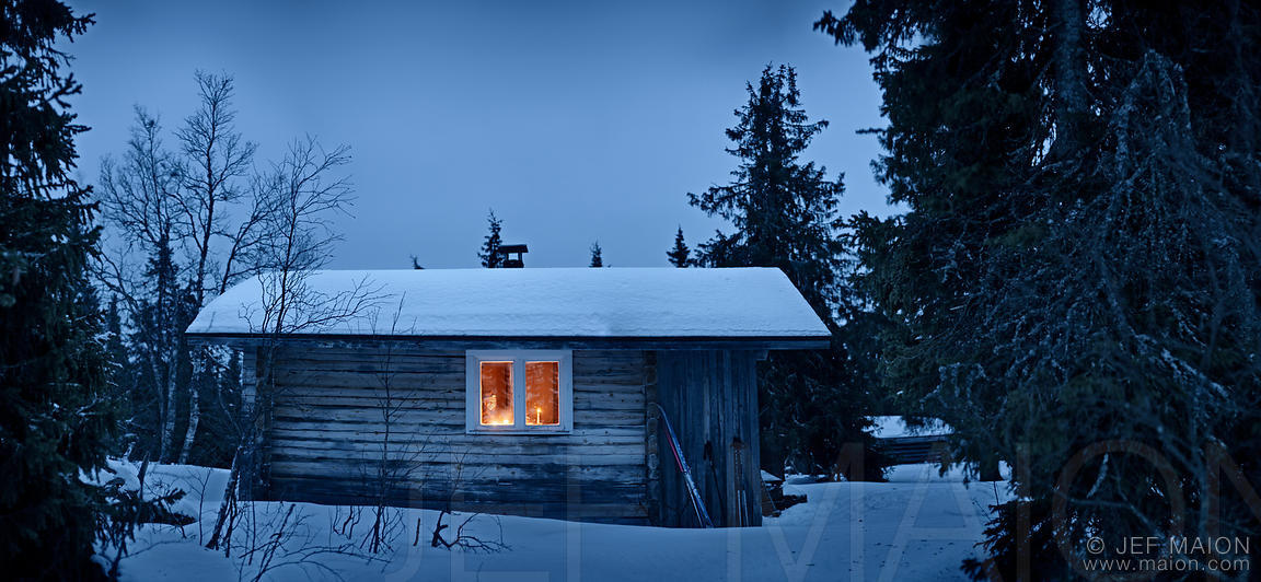Image: Forest hut lit by candles by winter night | Stock ...