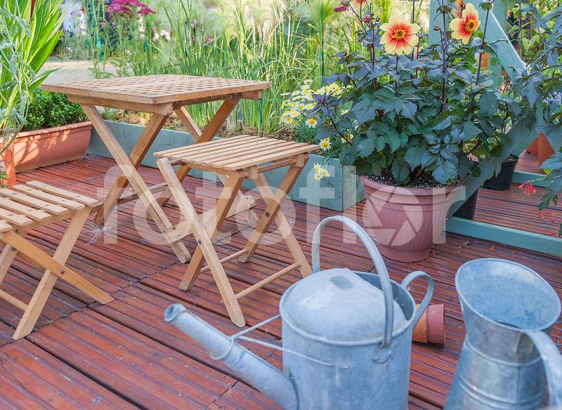Photo de Terrasse en bois avec petite table et tabouret, arrosoir en ...