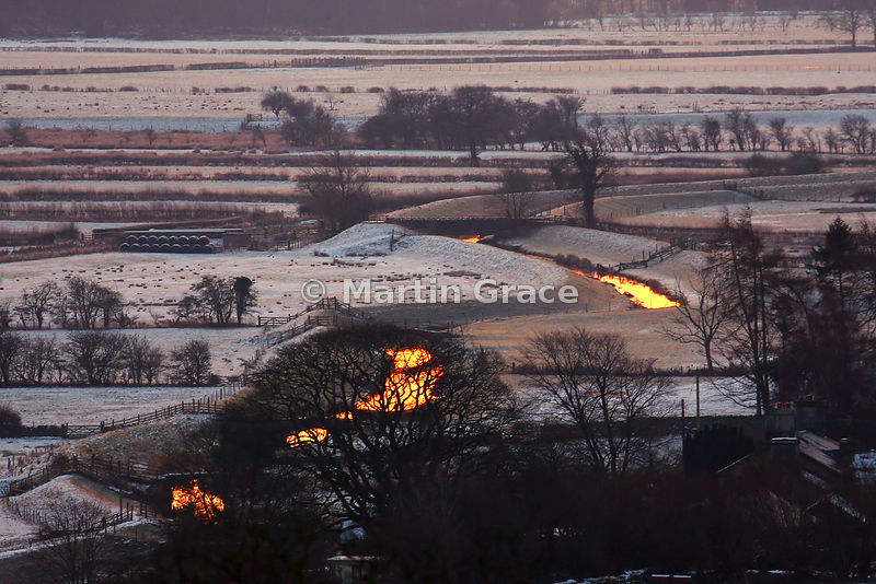 Snowy Lyth Valley at dawn in January with the burnished gold reflection of sunlight off the watercourse, English Lake District
