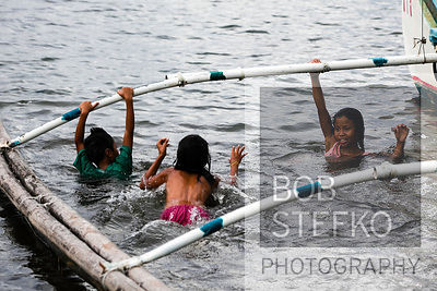 Children swimming next to pump boat on shore line of Taal Volcano Island, Lake Taal, Talisay, Batangas, Philippines