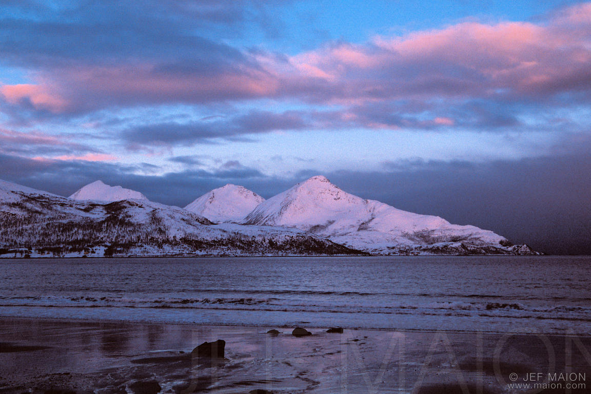 Dawn on snow-covered mountains by the Arctic Ocean