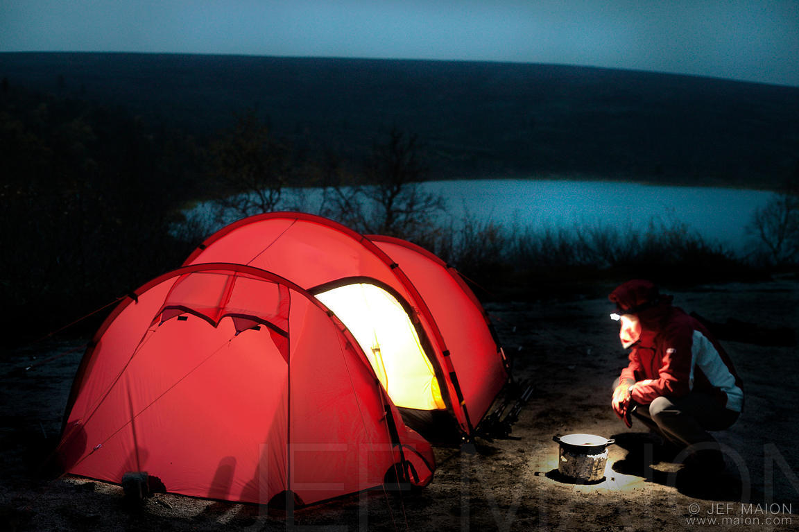 Backpacker cooking by tent by night & Image: Backpacker cooking by tent by night | Stock photo by JF Maion