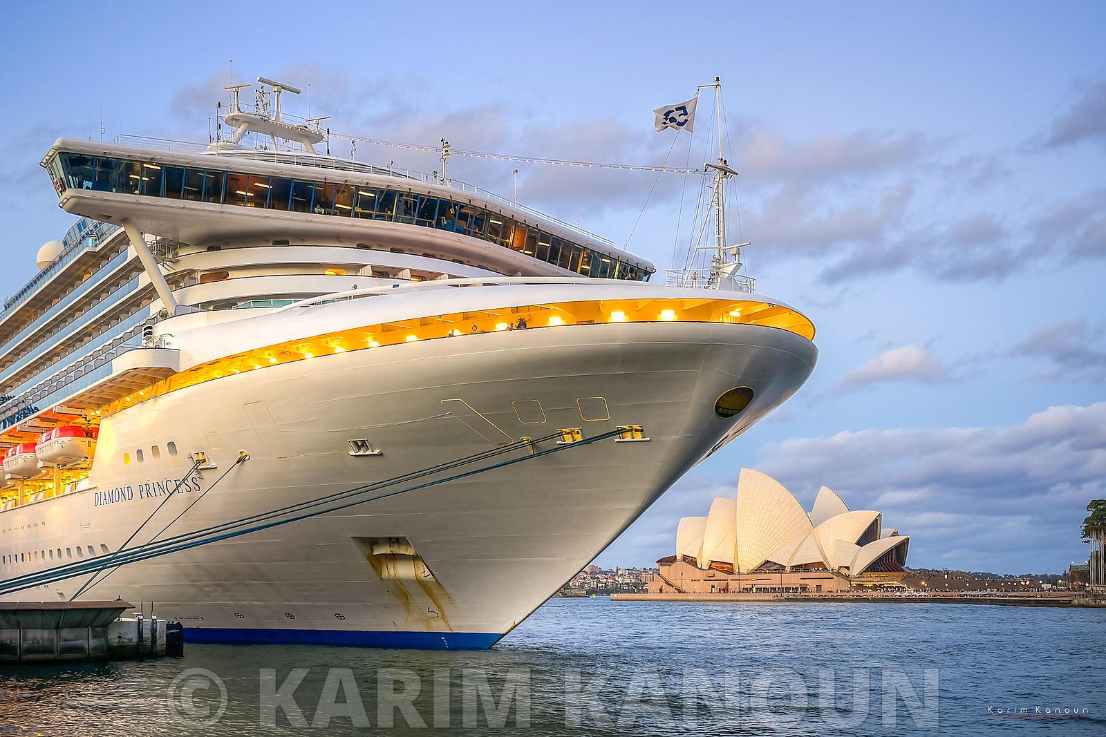 Sydney Opera House behind a cruising boat