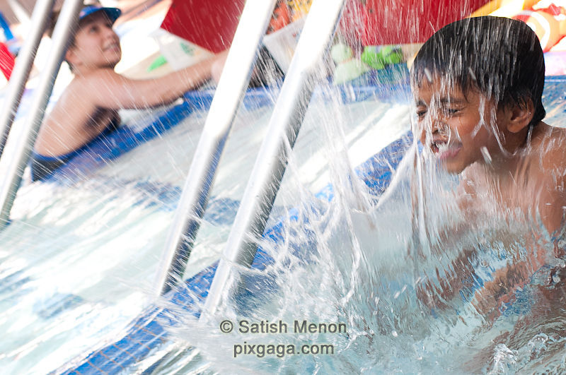 Boy splashing water in pool